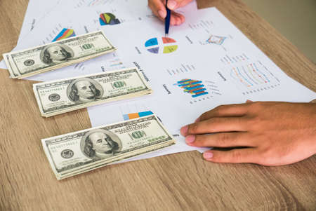 Closeup of Asian male right hand hold ball pen points on business charts under bunch of dollars banknotes for business, finance, tax and people concept