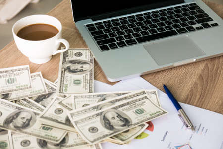 Closeup of bunch of dollars banknotes above colorful business charts nearby labtop and a cup of coffee on right side on wooden desk for business, finance, tax and people concept