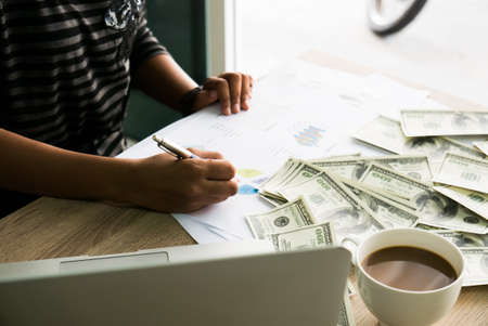 Closeup of Asian female writes something on business charts under bunch of dollars banknotes nearby her labtop and a cop of coffee for business, finance, tax and people concept Stock Photo