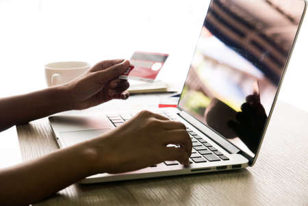 Asian female office worker typing on her laptop and holding credit card on left hand