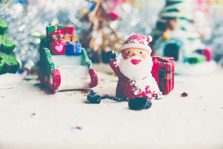Santa Claus, snowman, houses & snow Sledge miniature model studio shot on colorful background for family, giving, season, Christmas, holiday, new year, travel and gathering concept Standard-Bild