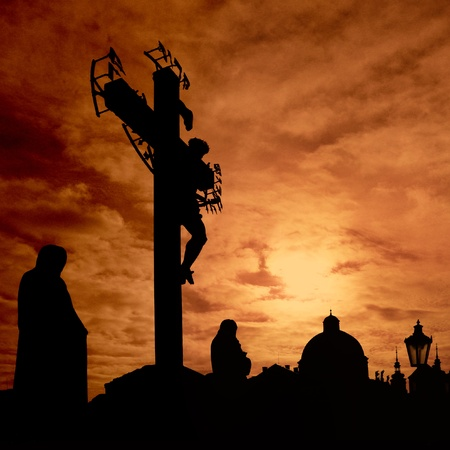 Dark silhouettes of Jesus Christ and monks are standing against burning red sunrise at Charles bridge, Prague                  Stockfoto