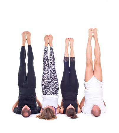 Practicing Yoga exercises in group   Shoulderstand - Sarvangasana - Viparita Karani photo