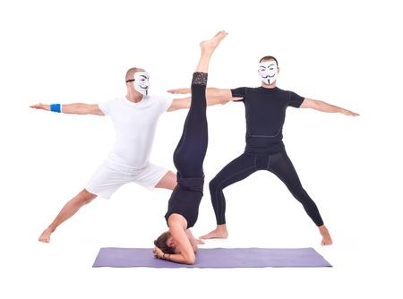virabhadrasana: The two masked men and girl doing  Yoga exercises in studio on white background   Pose name   Warrior Pose - Virabhadrasana   Headstand - Sirsasana