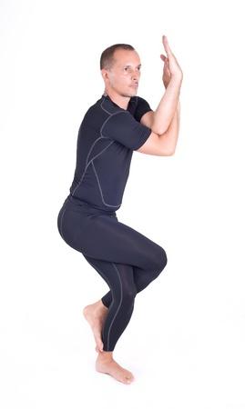 Man doing Yoga exercises in studio on white background   Pose name  Eagle Pose - Garudasana Reklamní fotografie