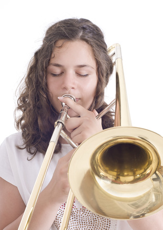 Teenage girl playing the trombone  Isolated on a white Studio shot photo