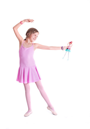 Cute little ballerina playing with her doll  Isolated on a white  photo