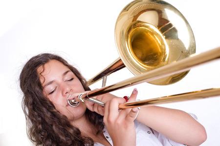 trombón: Adolescente que toca el tromb�n Aislado en un disparo de estudio de fondo blanco
