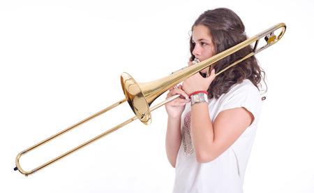 スタジオ撮影白い背景の上分離されたトロンボーンをプレイ 10 代の少女