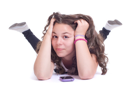 Teenage girl with mobile telephone  Isolated on a white background  Studio shot photo
