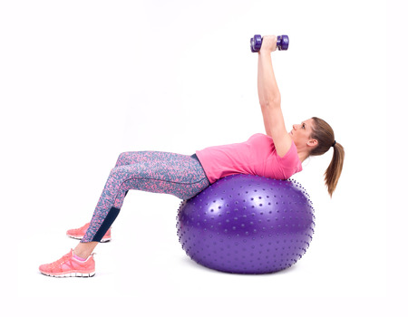 Sport woman exercising with a purple pilates ball and dumbbells  Isolated on a white background  Studio shot Reklamní fotografie
