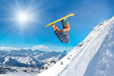 Extreme snowboarder jumping high in the air photo