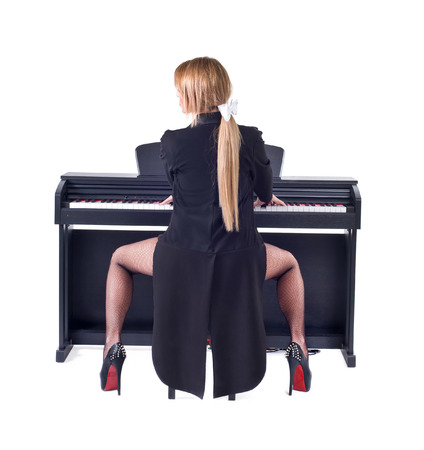 Beautiful blond girl playing piano  Isolated on a white background  Studio shot photo