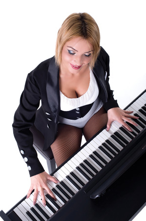 Beautiful blond girl playing piano Isolated on a white background photo