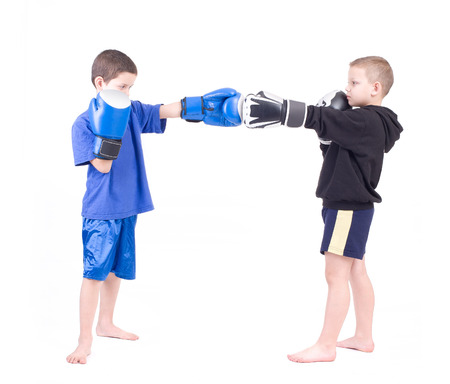 Two kids sparring  Isolated on a white background  Studio shot Reklamní fotografie