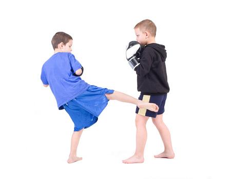 子供のキック ボクシングの戦い分離スタジオ撮影白い背景の上