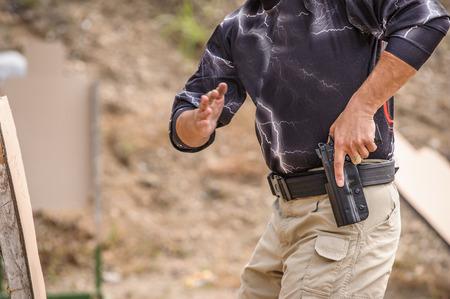 hombre disparando: Hombre que tira el arma en el entrenamiento, campo de tiro al aire libre Foto de archivo