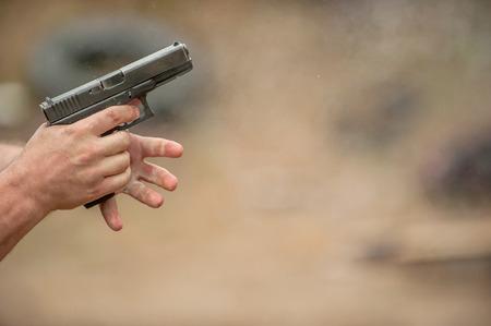 Man Changing Pistol Clip in Outdoor Shooting Range photo
