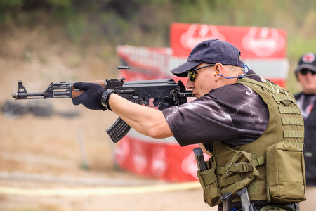 Man with Submachine Gun Shooting in Weapons Training, Outdoor Shooting Range photo