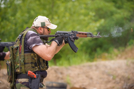 Man with Submachine Gun Shooting in Weapons Training, Outdoor Shooting Range photo