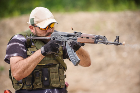 sports shell: Man with Submachine Gun Shooting in Weapons Training, Outdoor Shooting Range