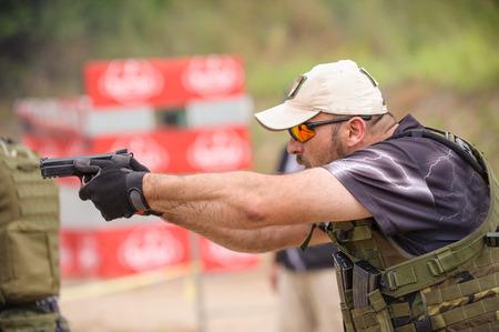 hombre disparando: Hombre Disparo en Campo de Tiro de Armas Outdoor Training Foto de archivo