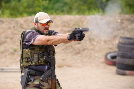 Man Shooting in Weapons Training Outdoor Shooting Range photo