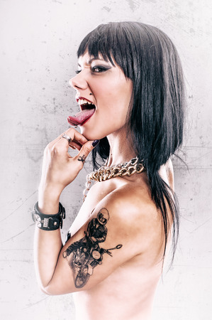 piercing: Grunge Tattoo Girl with Tongue Piercing Stock Photo