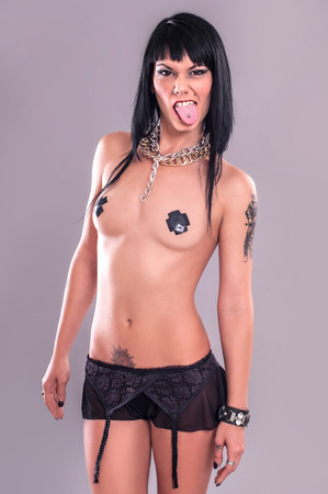 nude woman sex: Tattoo Girl with Tongue Piercing.  Aggressive and sexy tattoo lady with tongue piercing. Studio shoot. Stock Photo