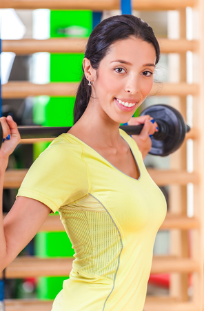 Pretty young woman practicing in the gym. A young woman in a health club photo