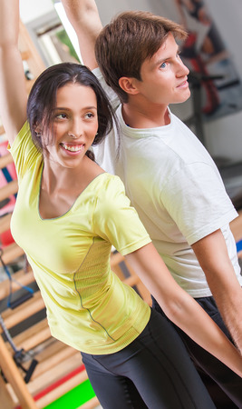Training instructor. Woman with personal trainer in gym photo