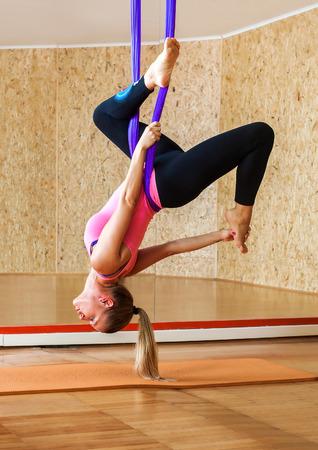 Woman doing antigravity Aerial yoga. Young woman making antigravity yoga exercises Reklamní fotografie