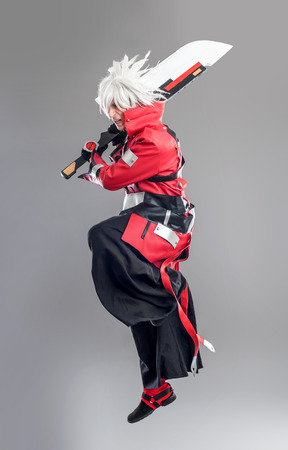 Manga hero with sword. A young man dressed in comic style superhero Stock Photo