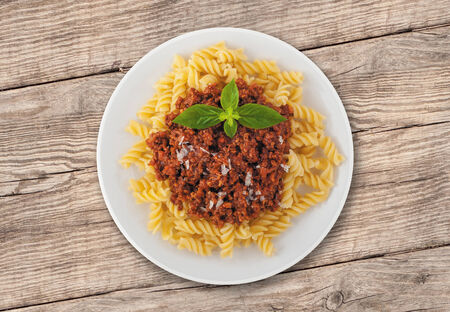 Spaghetti Bolognese with Basil Leaf. Tasty spaghetti dish with tomato sauce and parmesan cheese photo