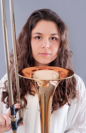 trombon: Adolescente con el trombón. Aislado en un fondo gris. Tiro del estudio