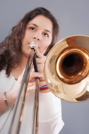 only teenage girls: Teenage girl with trombone. Isolated on a gray background. Studio shot