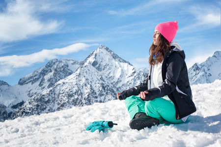 snow white: Beautiful young woman doing yoga in the snow mountains. Winter Scenic in the French Alps Les 2 Alpes Stock Photo