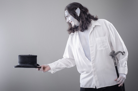 conjuring: Fantasy Illusionist Performer Bowing. Body painted performer in black and white suit bowing with hat and stick Stock Photo