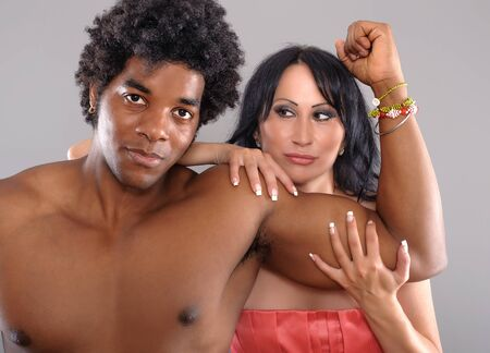 hot love: Strong Black Man showing biceps to woman. Woman putting hands around mans biceps