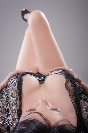 femme noire nue: Femme sexy posant en déshabillé. Belle sensuelle sexy jeune femme brune portant déshabillé noir transparent nuisette Banque d'images