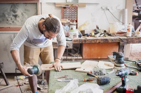 carpintero: Carpintero que usa la sierra circular Carpintero utilice mesa circular sierra eléctrica cortando madera en el taller Foto de archivo