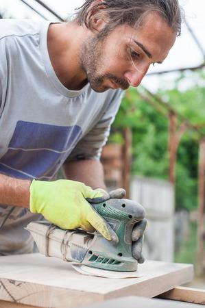 sander: Carpenter Using Electric Sander Carpenter sanding a wood with sander, outdoors Stock Photo