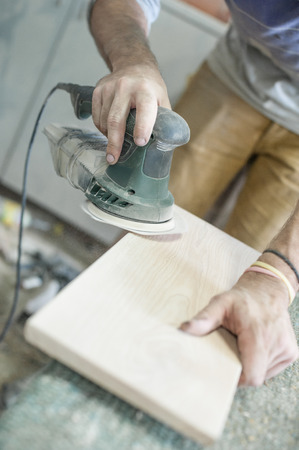 sander: Carpenter Using Electric Sander Carpenter sanding a wood with sander, outdoors Stock Photo
