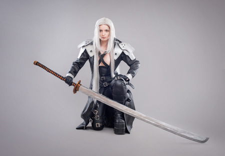Fantasy woman warrior. Woman warrior with sword and armor isolated on the gray background