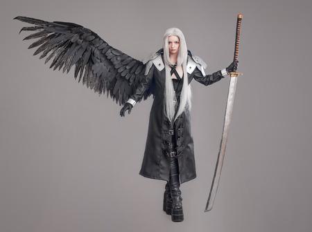 guerrero: Mujer de la fantas�a del guerrero Guerrero de la mujer con la espada y las alas aisladas en el fondo gris Foto de archivo