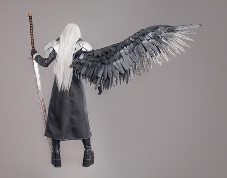 guerrero: Mujer de la fantasía del guerrero Guerrero de la mujer con la espada y las alas aisladas en el fondo gris Foto de archivo