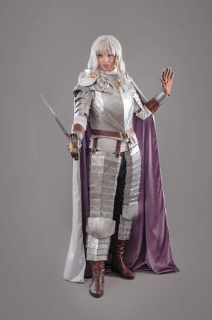 unrealistic: Female Knight In Shining Armour with sword isolated on the gray background Stock Photo