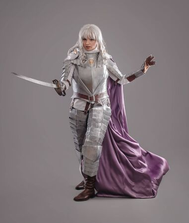 berserk: Female Knight In Shining Armour with sword isolated on the gray background Stock Photo