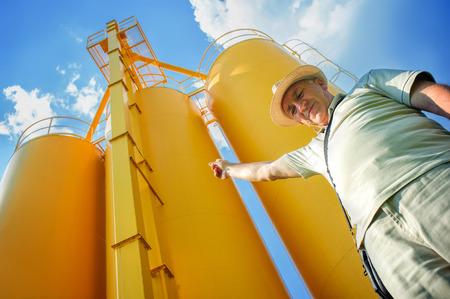 granjero: Farmer y silos. Un agricultor en su campo de trigo maduro, silos en el fondo