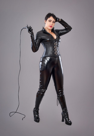 fancy dress costume: catwoman. Beautiful woman in catwoman leather latex whith whip